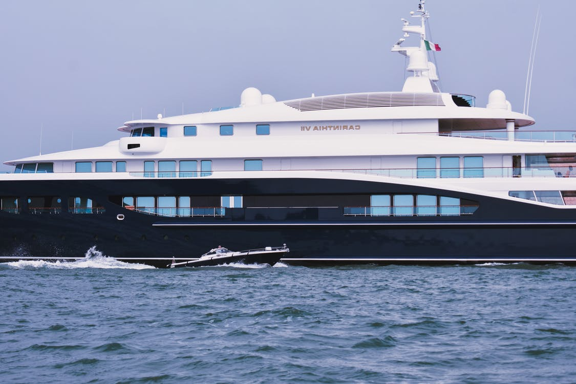 Luxury contemporary private yacht and small motorboat floating in blue ocean against cloudless sky