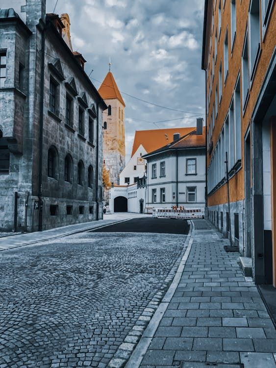 Empty street with old residential buildings leading to medieval tower located in old town in cloudy day