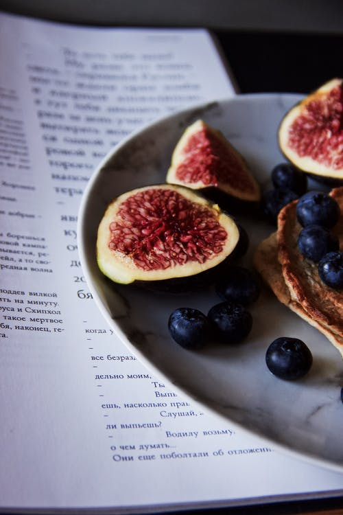 Half of plate with tasty sliced figs placed on plate near blueberries and pancakes on table near piece of paper