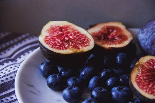 Halves of ripe figs placed on plate near blueberries on table with cloth in kitchen in daylight inside
