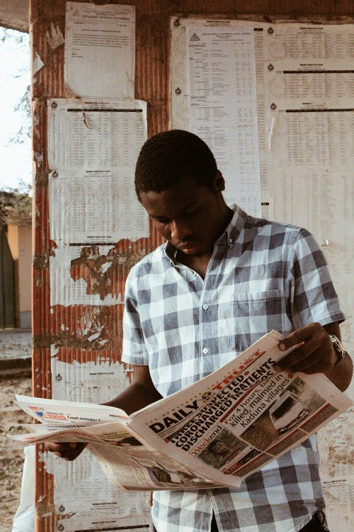 African American man with newspaper in daylight