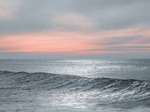Ocean Waves Under Cloudy Sky during Sunset
