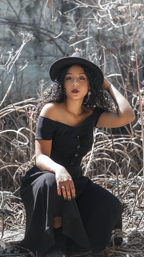 A Woman Wearing a Black Dress and a Black Hat