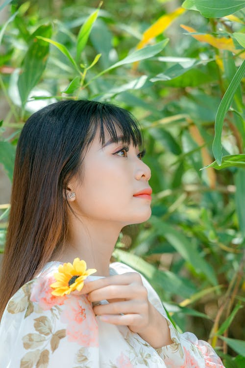 Woman in White Shirt Holding Yellow Flower