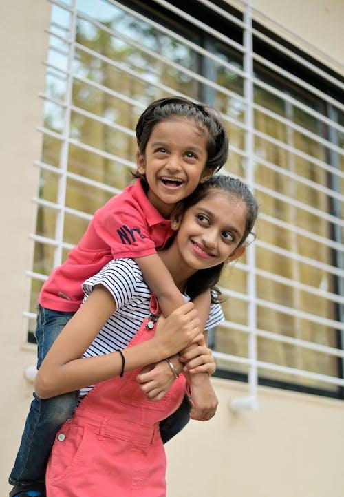 Happy ethnic children standing near building