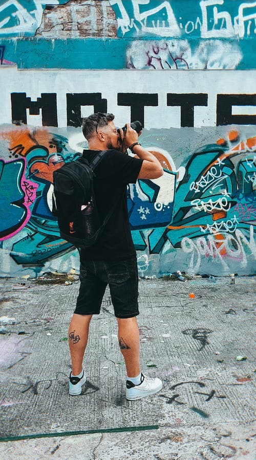 Back view of adult man with camera and backpack wearing casual clothes taking picture near graffiti wall