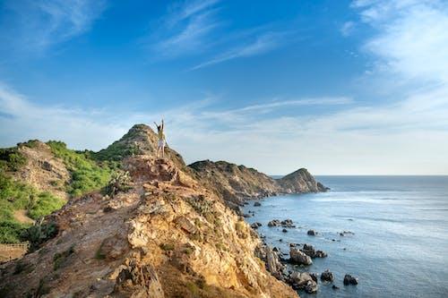 Unrecognizable person raising arms on rocky seacoast