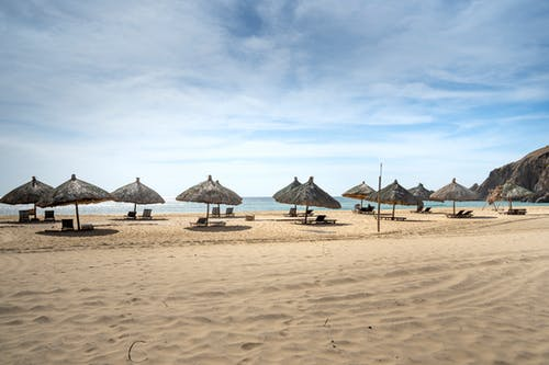 Spacious sandy beach with straw umbrellas and sunbeds near azure seawater beneath clear blue sky on hot summer day