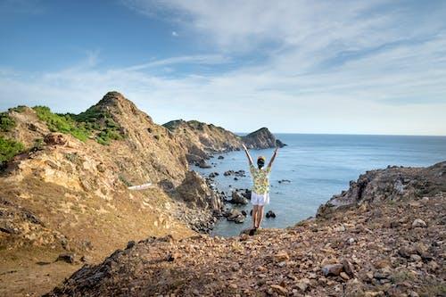 Unrecognizable person raising arms on rocky bay shore