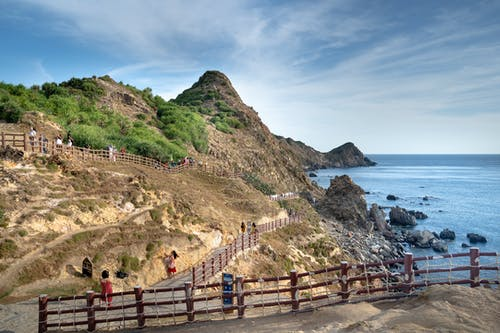Travelers strolling on wooden pathway on rough grassy cliff slope washed by azure rippling sea on hot summer day