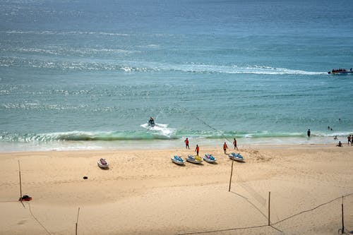 Relaxed people in life jackets walking on warm sandy beach near wave runners on sunny summer day