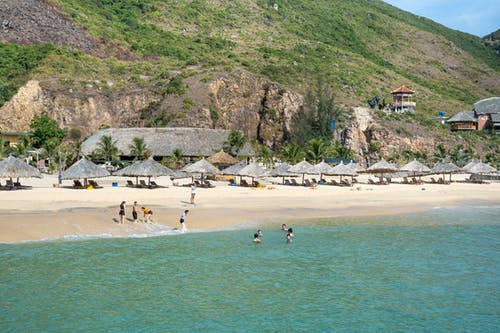 People chilling on sandy beach surrounded by grassy hills
