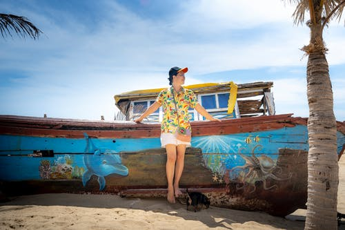 Full body barefoot content female in bright sunny clothes and cap leaning on old boat on sandy sunny beach and looking away with smile