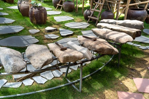 Thematic garden with big stones and hammers on metal rack near lush potted plants on grassland on sunny day