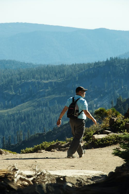 Side view of unrecognizable male traveler in casual clothes and backpack walking on trail during hiking in mountains covered with coniferous forests
