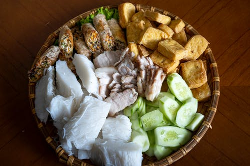 Top view of Asian food with rice noodles cucumber fried tofu and boiled pork with springs rolls served in bowl on table