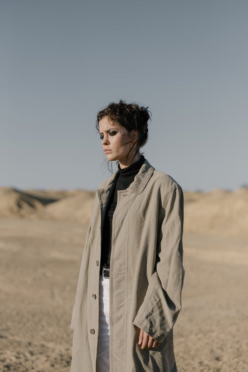 Woman in Brown Coat Standing on Brown Field