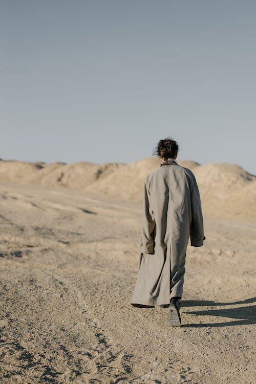 Man in Gray Coat Walking on Brown Sand