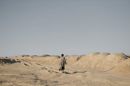 Man in Gray Jacket Walking on Brown Sand