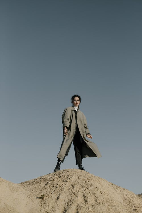 Man in Brown Coat Standing on Rock Under Blue Sky