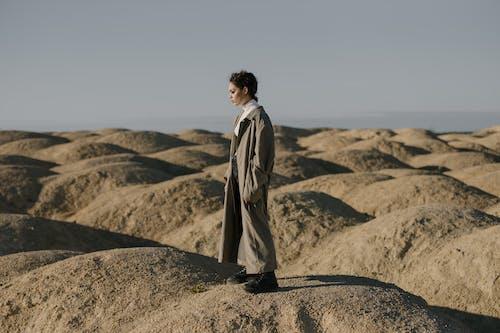 Man in Brown Coat Standing on Brown Sand