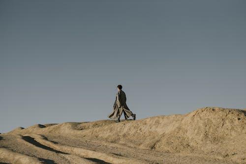 Man in Black Jacket Walking on Brown Sand
