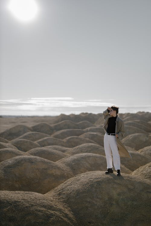 Woman in White Pants Standing on Brown Sand