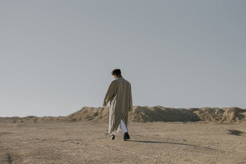 Man in White Thobe Walking on Brown Sand