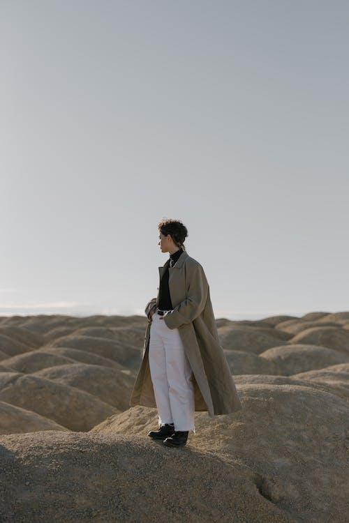 Man in Brown Coat Standing on Brown Rock