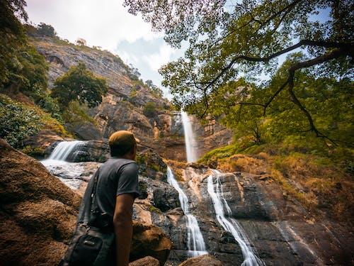Man in Black T-shirt Standing on Brown Rock Near Waterfalls