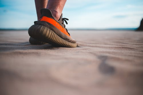 Crop man in stylish sneakers on sandy coast