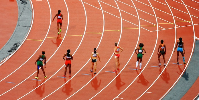 Women Standing on Race Track While Preparing for a Run Race during Daytime