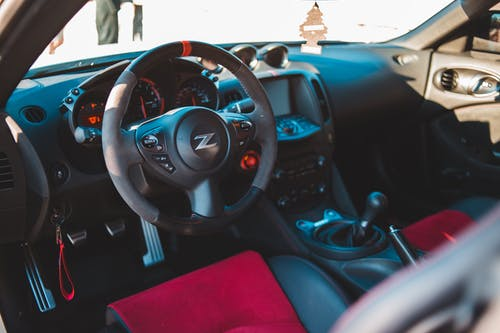 Inside of contemporary automobile with black leather interior with air freshener hanging near steering wheel and red seat cover in daylight in