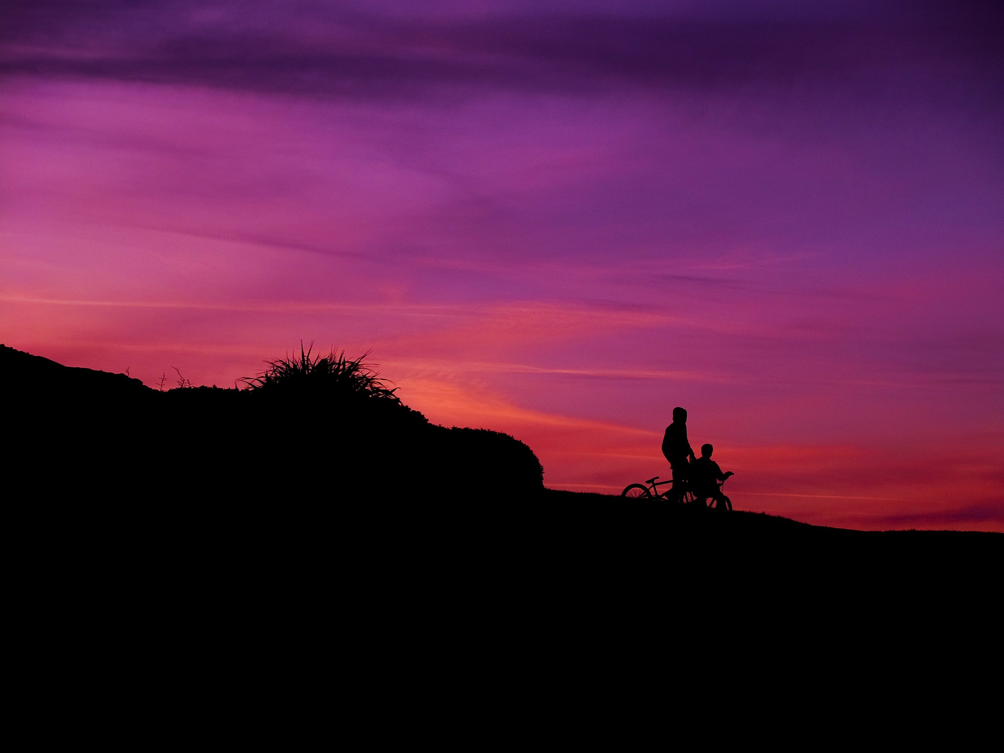 Bikers on Slope Silhouette during Sunset