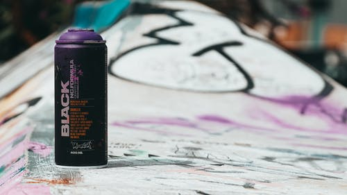 Spray can with paint placed on concrete skate ramp painted with graffiti signatures