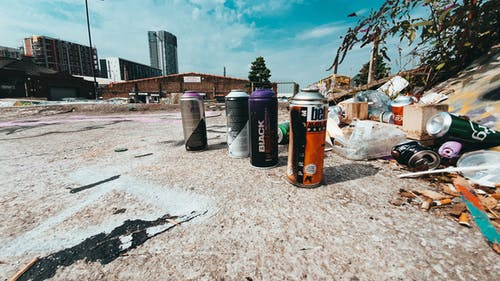 Spray cans with paint standing by small pile of trash on messy concrete road against cloudy sky and modern buildings