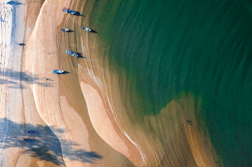 Aerial view of calm ocean with moored boats near wet sandy beach on sunny day