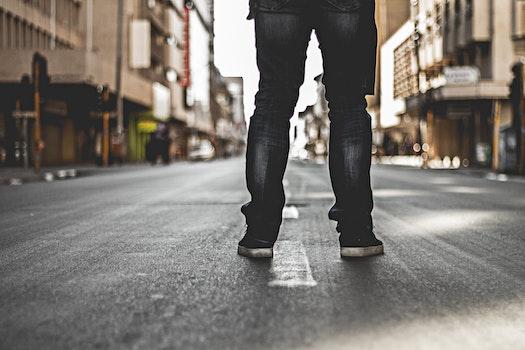 Man in Black Denim Jeans Standing on Grey Concrete Road