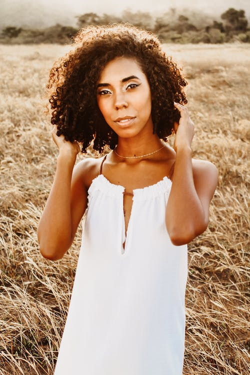 African American curly haired female on grassy meadow