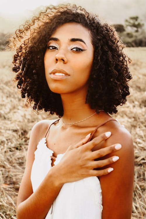 Attractive African American female with curly dark hair and makeup standing in grassy field and looking at camera