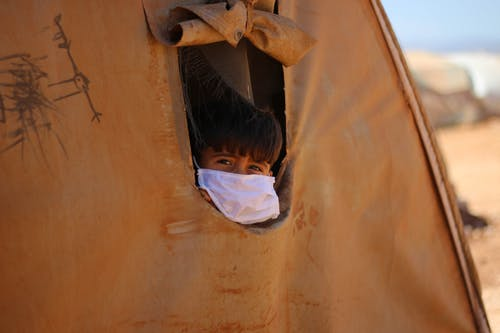 Boy in face mask looking out hole in tent