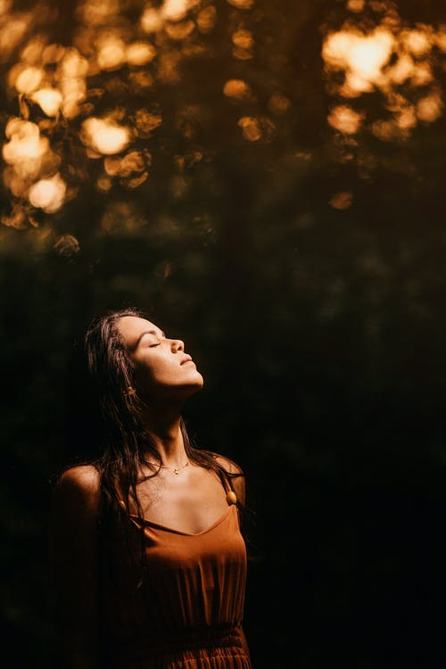 Serene woman with eyes closed standing in blurred nature