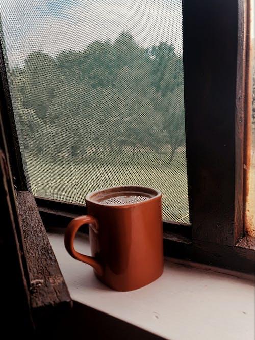 Red Ceramic Mug on Window