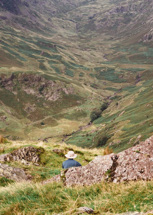 Person in Blue Jacket Sitting on Rock Mountain