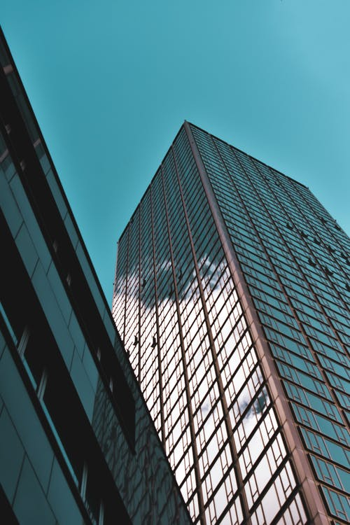 Low angle of skyscraper with glass mirrored windows near geometric building in downtown of megalopolis
