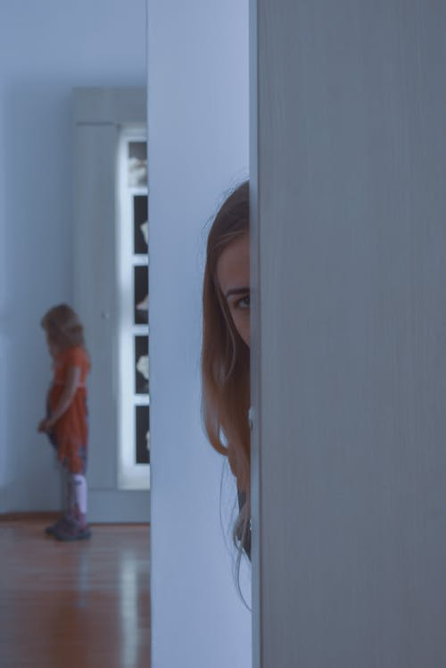 Young woman peeping and looking at child
