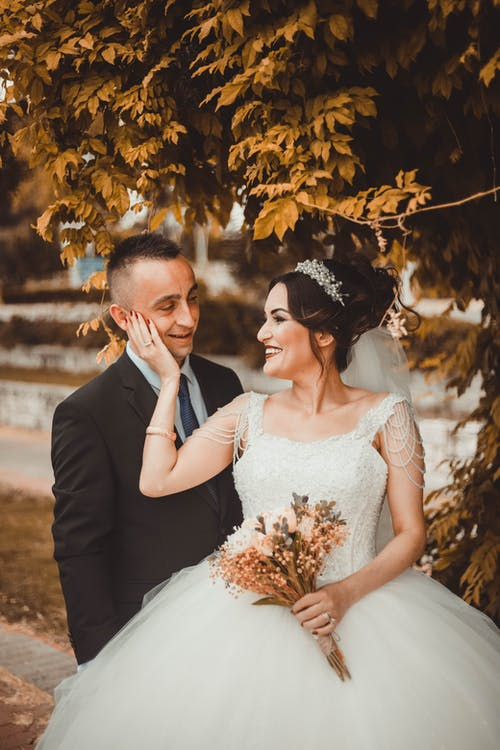 Happy wife touching face of husband while standing close under branches of tree and looking at camera