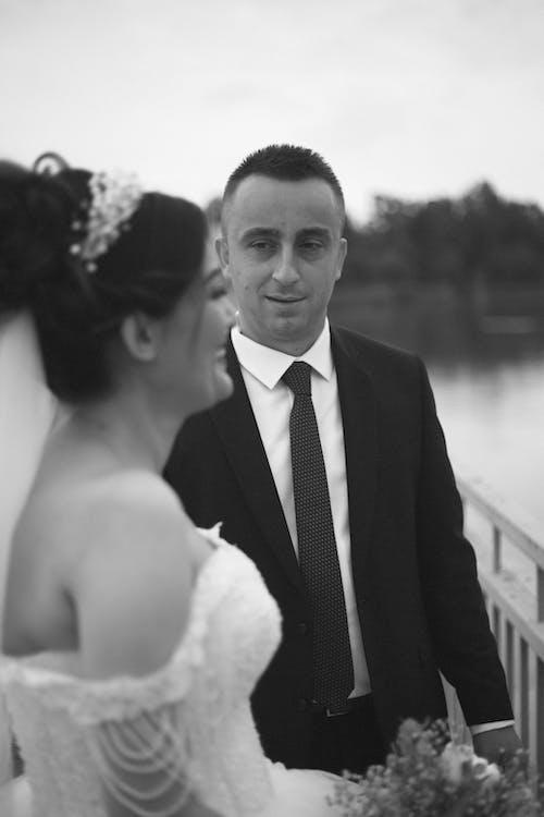 Groom standing near happy bride on waterfront