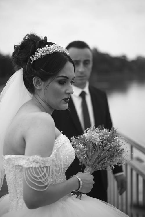 Serious bride with bouquet of flowers near groom