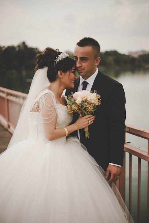 Gentle newlyweds embracing bridge under river